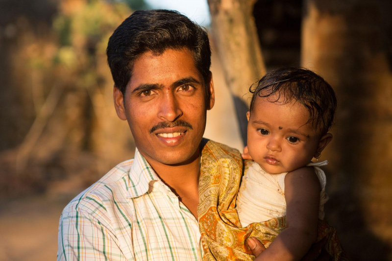 Indian man with his child on his arms